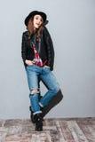 Retrato de la mujer joven confiada en sombrero y la chaqueta de cuero Foto de archivo libre de regalías