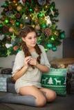 Retrato de la mujer joven contra la perspectiva de un árbol de navidad Imagen de archivo