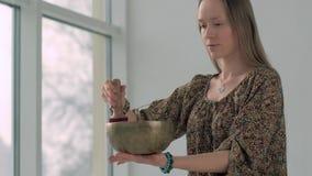 Retrato de la mujer joven de la yoga que juega el cuenco del canto antes de práctica de la yoga almacen de video