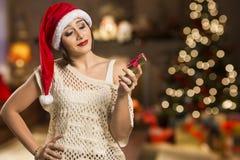 Retrato de la mujer joven decepcionada que sostiene el regalo de la Navidad Fotografía de archivo libre de regalías