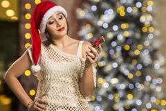 Retrato de la mujer joven decepcionada que sostiene el regalo de la Navidad Imagen de archivo