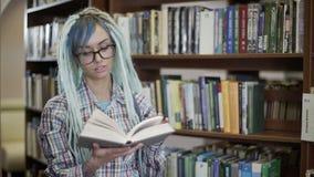 Retrato de la mujer joven del inconformista en vidrios con el libro de lectura de los dreadlocks delante de la cámara en sitio de almacen de video