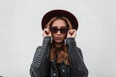 Retrato de la mujer joven del inconformista pelirrojo lujoso en gafas de sol de moda oscuras en sombrero p?rpura en chaqueta de c imagen de archivo