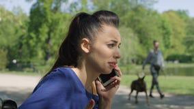 Retrato de la mujer joven del trastorno infeliz que habla en el teléfono móvil en parque soleado almacen de video