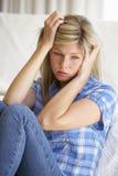 Retrato de la mujer joven deprimida en casa Fotos de archivo