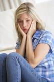Retrato de la mujer joven deprimida en casa Imagenes de archivo