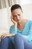 Retrato de la mujer joven deprimida en casa Imagen de archivo libre de regalías