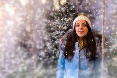Retrato de la mujer joven en abajo la chaqueta azul que se coloca en una nieve-c Fotos de archivo libres de regalías