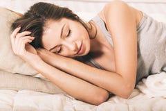 Retrato de la mujer joven en dormitorio en la cama solamente que se relaja fotos de archivo