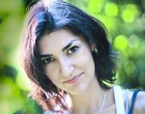Retrato de la mujer joven en el fondo verde del bokeh Fotos de archivo