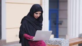 Retrato de la mujer joven en el hijab negro que se sienta en el banco de madera y que usa su ordenador portátil Retrato de jóvene almacen de metraje de vídeo