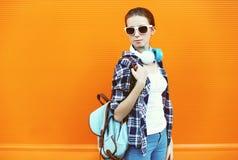 Retrato de la mujer joven en gafas de sol con los auriculares Foto de archivo