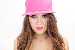 Retrato de la mujer joven en la camisa blanca y el sombrero rosado en el fondo blanco Cierre para arriba Foto de archivo