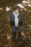 Retrato de la mujer joven en las hojas de otoño foto de archivo