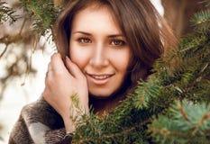 Retrato de la mujer joven en tela escocesa detrás del árbol de abeto Fotografía de archivo libre de regalías