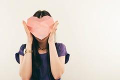 Retrato de la mujer joven en vidrios con un corazón en sus manos Amor Foto de archivo