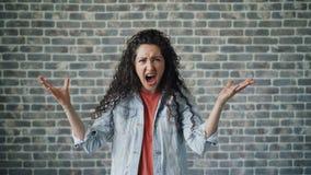 Retrato de la mujer joven enojada que grita con la cólera que se coloca en fondo del ladrillo almacen de video