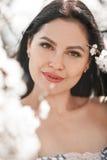 Retrato de la mujer joven entre ramas florecientes del albaricoquero Foto de archivo