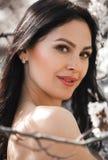 Retrato de la mujer joven entre ramas florecientes del albaricoquero Fotos de archivo libres de regalías