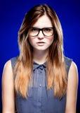 Retrato de la mujer joven estricta con los vidrios del empollón Fotografía de archivo