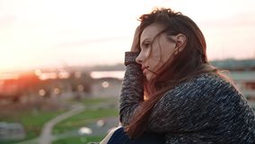 Retrato de la mujer joven europea triste hermosa en el tejado o balcón o terraza que disfruta de puesta del sol almacen de video