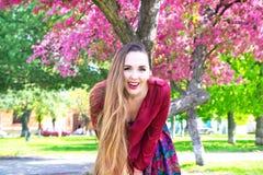 Retrato de la mujer joven feliz con el pelo largo que sonríe en cámara delante de Sakura Foto de archivo