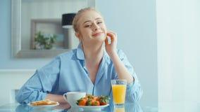 Retrato de la mujer joven feliz durante el desayuno almacen de video