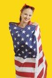 Retrato de la mujer joven feliz envuelta en bandera americana sobre fondo amarillo Fotos de archivo libres de regalías