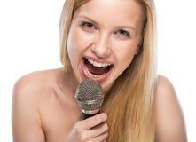 Retrato de la mujer joven feliz que canta con el micrófono Imagenes de archivo