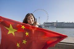 Retrato de la mujer joven feliz que celebra la bandera china contra el ojo de Londres en Londres, Inglaterra, Reino Unido Foto de archivo libre de regalías