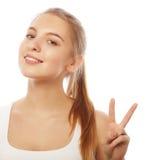 Retrato de la mujer joven feliz que da el signo de la paz Fotos de archivo