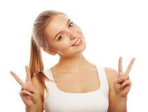 Retrato de la mujer joven feliz que da el signo de la paz Foto de archivo libre de regalías