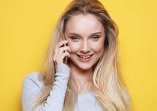 Retrato de la mujer joven, feliz que habla en el teléfono que mira la cámara, sobre fondo amarillo Imagen de archivo libre de regalías