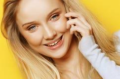 Retrato de la mujer joven, feliz que habla en el teléfono que mira la cámara, sobre fondo amarillo Foto de archivo