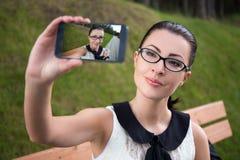 Retrato de la mujer joven feliz que hace la foto del selfie Fotos de archivo