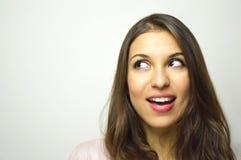 Retrato de la mujer joven feliz que mira al lado con curiosidad en el fondo blanco Copie el espacio imagen de archivo