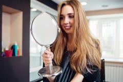 Retrato de la mujer joven feliz que mira en el espejo que se sienta en un salón de belleza Imagen de archivo
