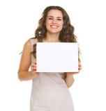 Retrato de la mujer joven feliz que muestra el papel en blanco Fotografía de archivo libre de regalías