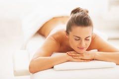 Retrato de la mujer joven feliz que pone en la tabla del masaje Imagenes de archivo