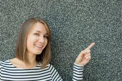 Retrato de la mujer joven feliz que señala en el espacio de la copia Fotos de archivo