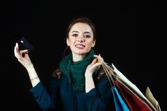 Retrato de la mujer joven feliz que sostiene la tarjeta de crédito y los bolsos coloridos que miran la cámara Imagenes de archivo
