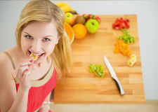 Retrato de la mujer joven feliz que tiene una mordedura mientras que corta la ensalada Foto de archivo libre de regalías