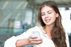 Retrato de la mujer joven feliz que usa el teléfono móvil Foto de archivo libre de regalías