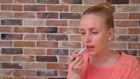 Retrato de la mujer joven hermosa con la cara limpia que aplica el lápiz labial almacen de metraje de vídeo