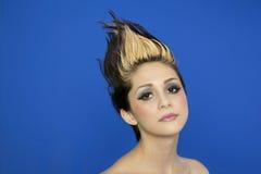 Retrato de la mujer joven hermosa con el pelo claveteado que presenta sobre fondo azul Fotos de archivo