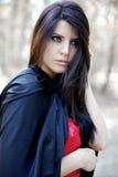 Retrato de la mujer joven hermosa con la capa negra en bosque mágico fotos de archivo libres de regalías