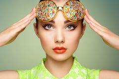 Retrato de la mujer joven hermosa con los vidrios coloreados Fotos de archivo libres de regalías