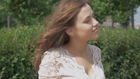 Retrato de la mujer joven hermosa con sonrisa atractiva En el verano en un día soleado almacen de metraje de vídeo
