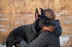 Retrato de la mujer joven hermosa con su perro del doberman Foto de archivo libre de regalías