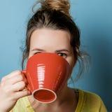 Retrato de la mujer joven hermosa con una taza roja en un backg azul Foto de archivo